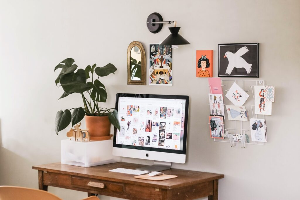 Picture of a wooden desk with a house plant and soft pictures